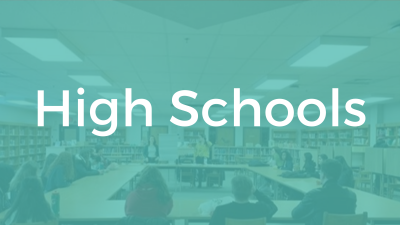 High Schools. Image: Students sitting around a large circle of tables.