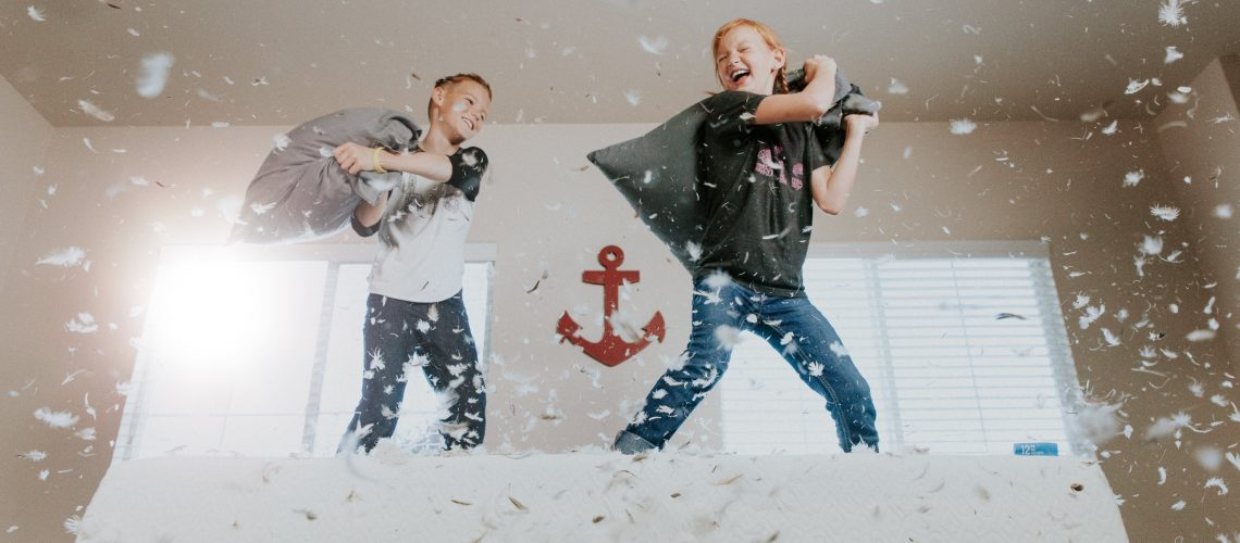 Two middle age children in a pillow fight.