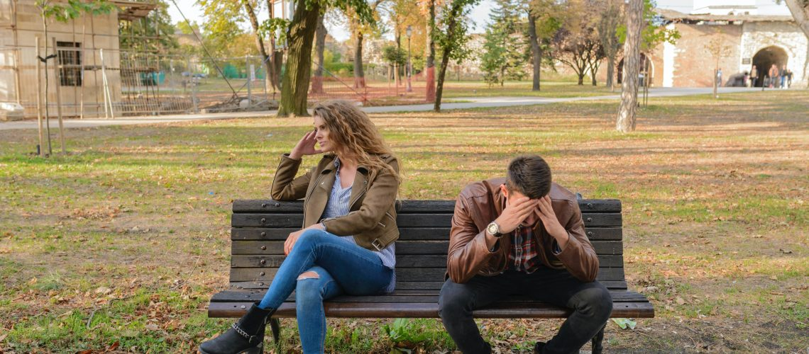 Two people sitting on a park bench, distraught.
