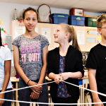 Youth stand in a semi-circle holding a web of yarn, smiling.