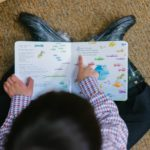 An overhead shot of a boy reading a picture book.