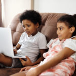 two children sit on a brown couch with a laptop