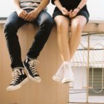 two teens sitting on a bench, legs dangling off the edge