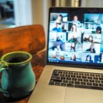 Zoom call on laptop screen placed beside a teal mug on a wooden desk.