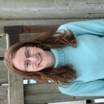 Haley Bauman wearing bright blue turtleneck sweater standing in front of a wood fence.