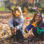 Two young children playing in the leaves.