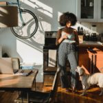 Black woman with coffee near dog standing in kitchen.
