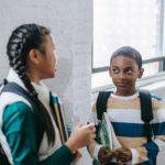 Positive diverse schoolchildren standing in corridor and talking