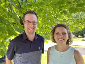Ben Janzen and Amy Zavitz standing together under a tree on a sunny day.