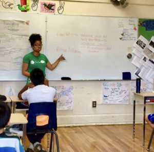 TREE Facilitator Kai is wearing a green TREE t-shirt, and is speaking to a group of students in a classroom.