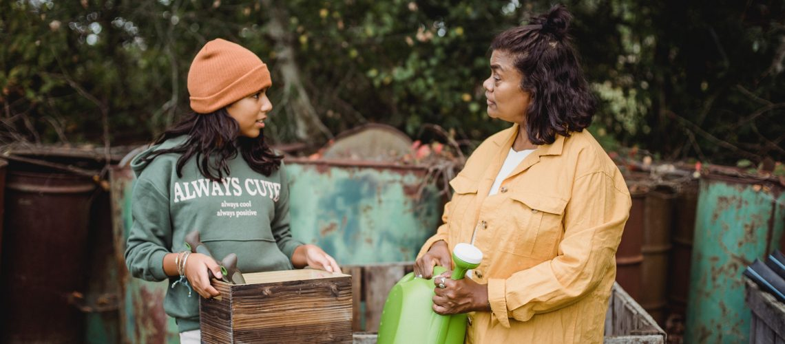 Ethnic mother talking to daughter with gardening tools