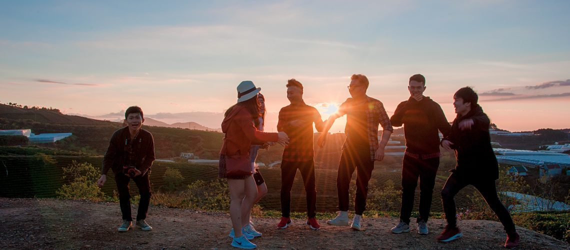 A group of teens gathered, laughing at sunset.