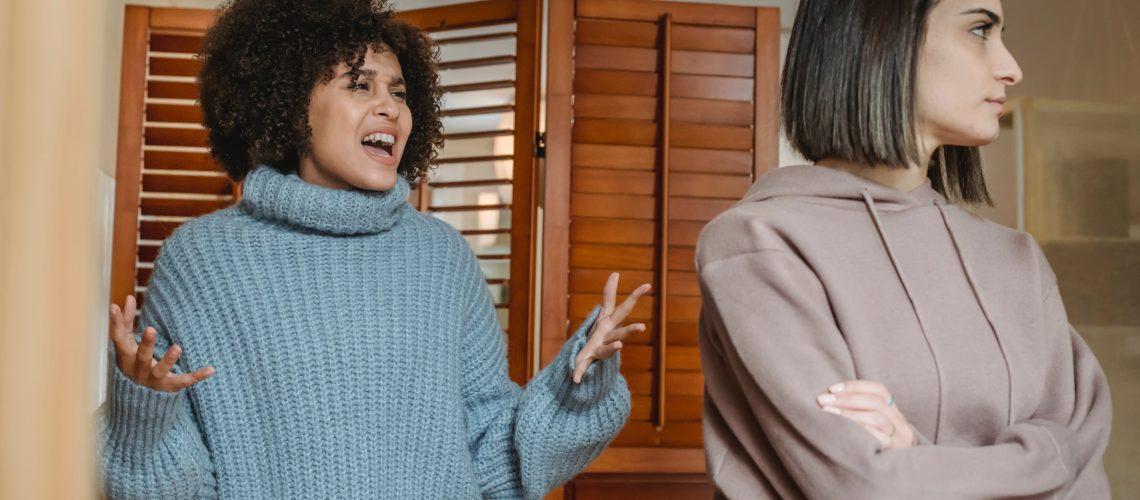 Multiethnic upset women scolding in room